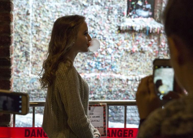Visitors chew gum and pose for photos near the gum wall in Post Alley at the Pike Place Market in Seattle, Washington on November 11, 2015. (JASON REDMOND/AFP/Getty Images)