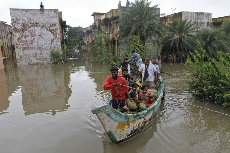 Volunteers rescue flood affected people on a country boat from a residential area in Chennai, India, Thursday, Dec. 3, 2015. The heaviest rainfall in more than 100 years has devastated swathes of the southern Indian state of Tamil Nadu, with thousands forced to leave their submerged homes and schools, offices and a regional airport shut for a second day Thursday.( AP Photo)