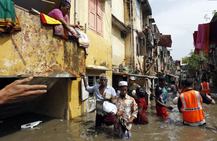 Flood-affected people receive food packets being distributed by navy personnel in Chennai, in the southern Indian state of Tamil Nadu, Friday, Dec. 4, 2015. The relentless rains that lashed the state for three days eased Friday, but the misery of tens of thousands of people was far from over, with large parts of the main city still underwater along with the region's biggest airport. (AP Photo/Arun Sankar K)