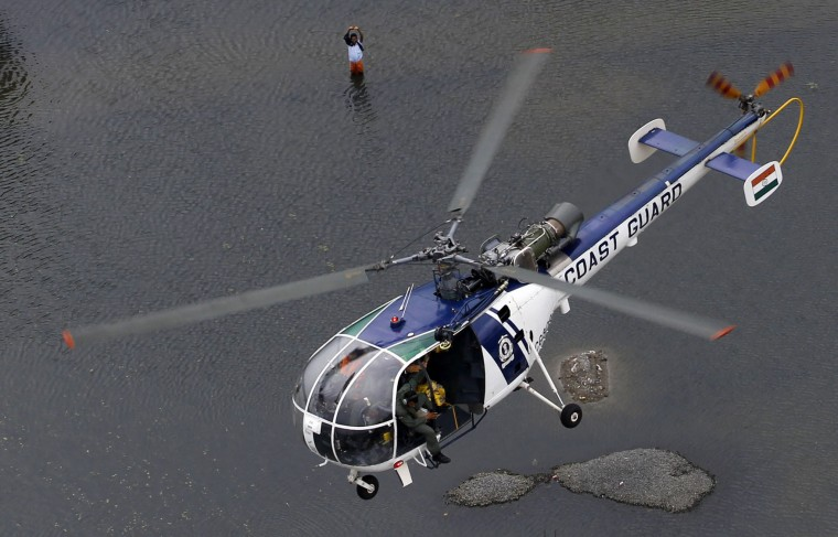 A flood-affected man waves to a coastguard chopper in Chennai, India, Saturday, Dec. 5, 2015. Although floodwaters have begun to recede, vast swaths of Chennai and neighboring districts were still under 2 1/2 to 3 meters (8 to 10 feet) of water, with tens of thousands of people in state-run relief camps. (AP Photo/Arun Sankar K)