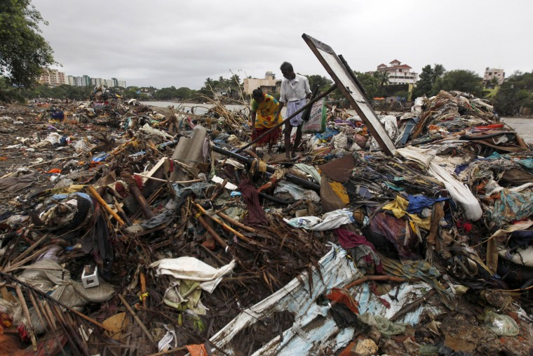 Residents try to salvage reusable material from their flood damaged houses on the banks of the Adyar River in Chennai, India, Sunday, Dec. 6, 2015. Indian authorities were investigating possible negligence after 18 hospital patients died when rainwaters from massive floods in southern Tamil Nadu state knocked out generators and switched off ventilators.The worst flooding in a century in Tamil Nadu has left scores of people dead since November. (AP Photo/Arun Sankar K)