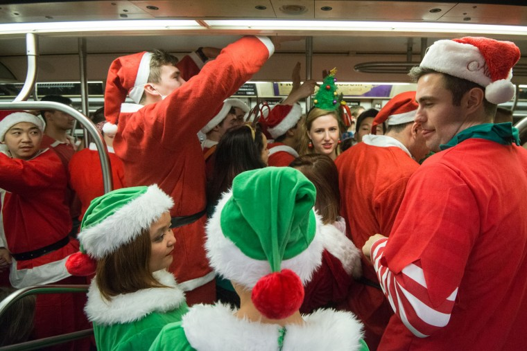 People dressed as Santas board a crowded subway during the annual SantaCon pub crawl December 12, 2015 in the Brooklyn borough of New York City. Hundreds of revelers take part in the holiday pub crawl, though some local bars and businesses have banned participants in an effort to avoid the typically rowdy SantaCon crowds. (Stephanie Keith/Getty Images)