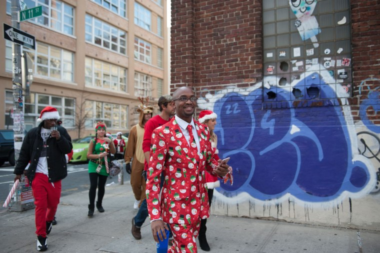 People dressed in holiday garb walk through the streets of Williamsburg during the annual SantaCon pub crawl December 12, 2015 in the Brooklyn borough of New York City. Hundreds of revelers take part in the holiday pub crawl, though some local bars and businesses have banned participants in an effort to avoid the typically rowdy SantaCon crowds. (Stephanie Keith/Getty Images)