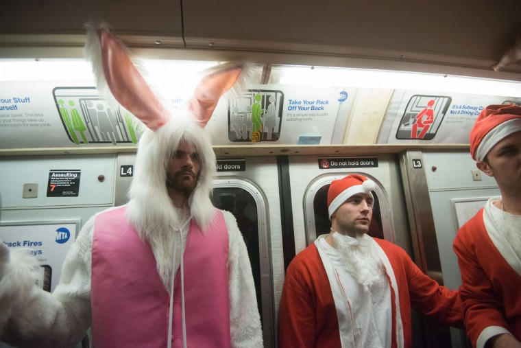 Men dressed as a Santa ride the subway with a man dressed as the Easter Bunny during the annual SantaCon pub crawl December 12, 2015 in the Brooklyn borough of New York City. Hundreds of revelers take part in the holiday pub crawl, though some local bars and businesses have banned participants in an effort to avoid the typically rowdy SantaCon crowds. (Stephanie Keith/Getty Images)