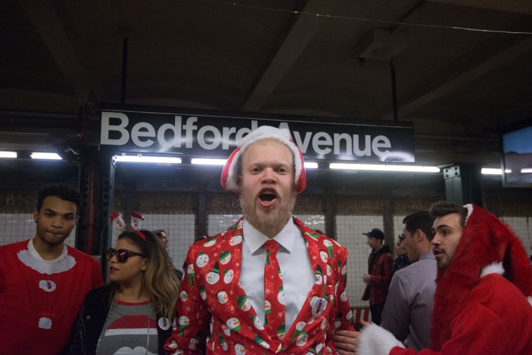 A man dressed in holiday garb waits for the subway on the platform during the annual SantaCon pub crawl December 12, 2015 in the Brooklyn borough of New York City. Hundreds of revelers take part in the holiday pub crawl, though some local bars and businesses have banned participants in an effort to avoid the typically rowdy SantaCon crowds. (Stephanie Keith/Getty Images)