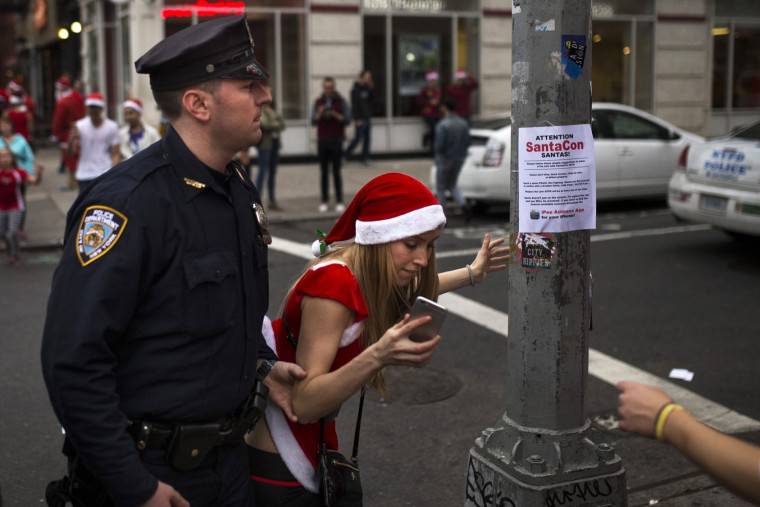 A police officer removes a reveler from standing on a post as they guard and clear the street of revelers dressed in holiday themed costumes during SantaCon in New York Saturday, Dec. 12, 2015, in New York. (AP Photo/Andres Kudacki)