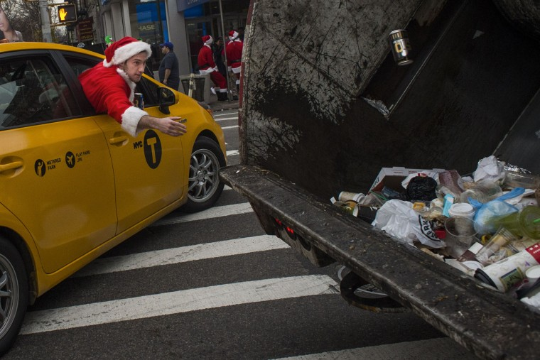 A reveler dressed in a holiday themed costume throws an empty can of beer inside a garbage truck as he participates in SantaCon in New York, Saturday, Dec. 12, 2015. (AP Photo/Andres Kudacki)