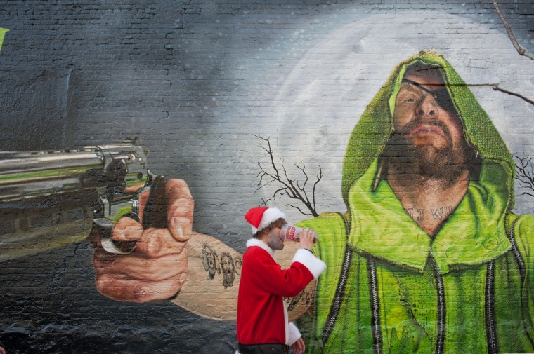 A man dressed as a Santa walks past a mural in Williamsburg during the annual SantaCon pub crawl December 12, 2015 in the Brooklyn borough of New York City. Hundreds of revelers take part in the holiday pub crawl, though some local bars and businesses have banned participants in an effort to avoid the typically rowdy SantaCon crowds. (Stephanie Keith/Getty Images)