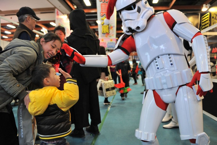 "A local fan dressed as a Christmas-themed Stormtrooper high-fives a child during a toy exhibition in Taipei on December 17, 2015. Ever since 1977, when ""Star Wars"" introduced the world to The Force, Jedi knights, Darth Vader, Wookiees and clever droids R2-D2 and C3PO, the sci-fi saga has built a devoted global fan base that spans the generations. (Sam Yeh/AFP/Getty Images)"