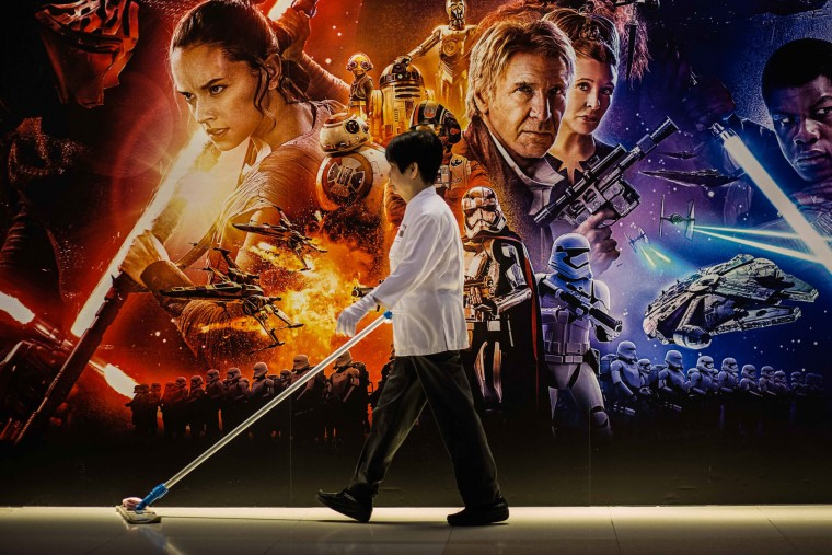 "A cleaner walks past a poster advertising ""Star Wars: The Force Awakens"" in Hong Kong on December 17, 2015. It may be one of the most hyped films of all time, but ""Star Wars: The Force Awakens"" opened on December 16 to ecstatic reviews from both fans and critics. (Anthony Wallace/AFP/Getty Images)"