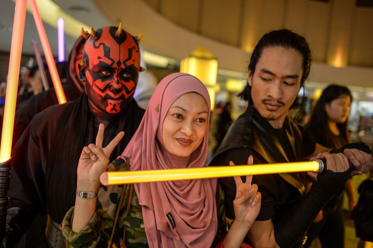 A Malaysian Muslim woman (C) poses for pictures with members of Malaysia's Star Wars Fan Club dressed as various characters before watching 'Star Wars: The Force Awakens' at a cinema in Subang, outside Kuala Lumpur on December 17, 2015. (Mohd Rafsan/AFP/Getty Images)