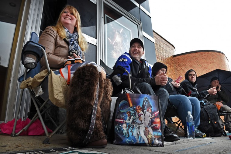Alley Shelley, of Parkville, from left, and friend Steve Schneider, of Dundalk, arrived at 7 a.m. to start the line for the 7 p.m. premiere of Star Wars: The Force Awakens at the Senator Theater. Shelley made the Chewbacca leg warmers and brought along Star Wars themed snacks in her Star Wars bag. (Kenneth K. Lam/Baltimore Sun)