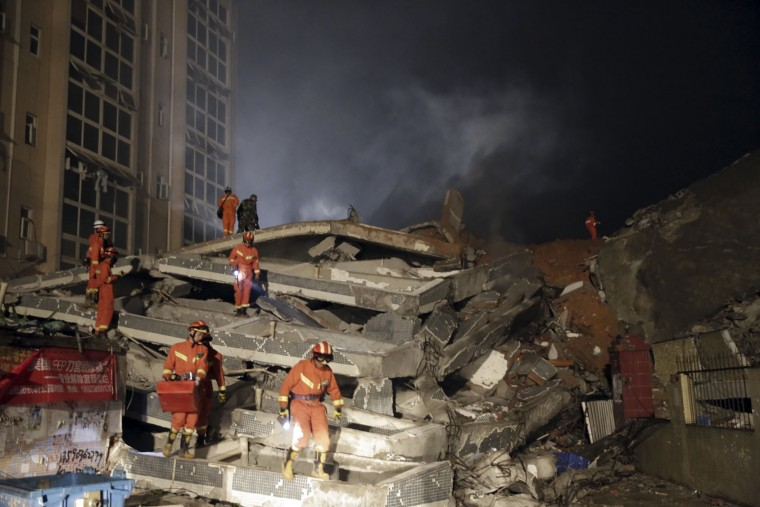 Rescuers search for survivors amongst collapsed buildings in the aftermath of a landslide in Shenzhen in south China's Guangdong province Sunday Dec. 20, 2015. The landslide collapsed and buried buildings at and around an industrial park in the southern Chinese city of Shenzhen on Sunday, leaving many missing, authorities said. (Color China Photo via AP)