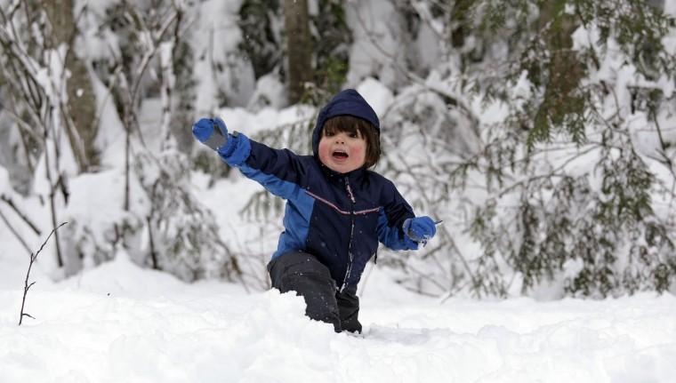 Conner Perkins, 2, smiles as he plays in freshly-fallen snow, Tuesday, Dec. 22, 2015, at Snoqualmie Pass, Wash. A weather pattern that could be associated with El Nino has turned winter upside-down across the U.S. during a week of heavy holiday travel, bringing spring-like warmth to the Northeast, a risk of tornadoes in the South and so much snow in parts of the West that there are concerns about avalanches. On Christmas Day, it could be warmer in New York City than Los Angeles. (AP Photo/Elaine Thompson)