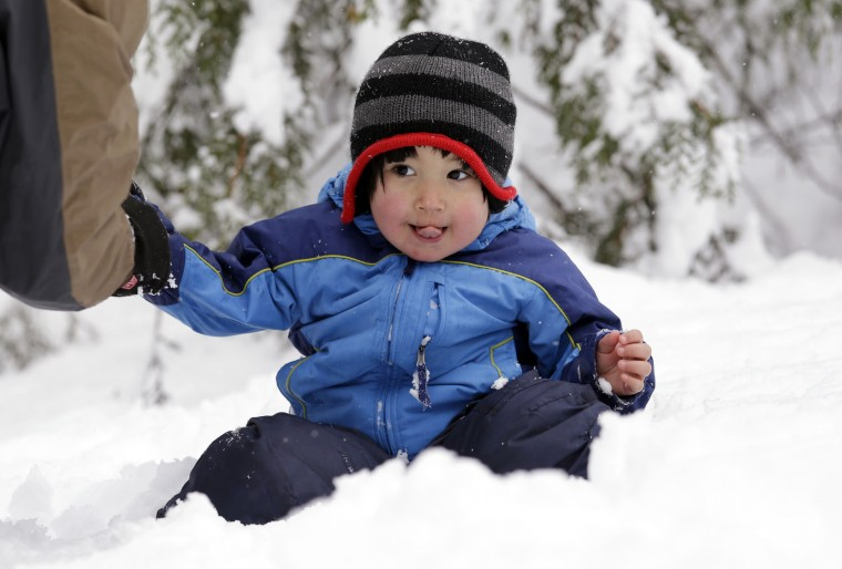 Leon Perkins, 3, sits in a snowbank as his father helps him put on mittens Tuesday, Dec. 22, 2015, at Snoqualmie Pass, Wash. The Seattle family headed to the mountains Tuesday to enjoy the new snow that fell overnight. A weather pattern that could be associated with El Nino has turned winter upside-down across the U.S. during a week of heavy holiday travel, bringing spring-like warmth to the Northeast, a risk of tornadoes in the South and so much snow in parts of the West that there are concerns about avalanches. On Christmas Day, it could be warmer in New York City than Los Angeles.(AP Photo/Elaine Thompson)
