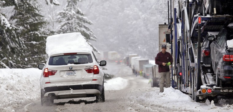 A car still topped by snow drives down an onramp and past trucks stopped to remove chains after making the drive across Snoqualmie Pass, Wash., Tuesday, Dec. 22, 2015. A weather pattern that could be associated with El Nino has turned winter upside-down across the U.S. during a week of heavy holiday travel, bringing spring-like warmth to the Northeast, a risk of tornadoes in the South and so much snow in parts of the West that there are concerns about avalanches. On Christmas Day, it could be warmer in New York City than Los Angeles. (AP Photo/Elaine Thompson)