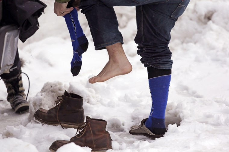 A snowshoer changes socks and shoes before starting out on a trek in freshly-fallen snow at Snoqualmie Pass, Wash., Tuesday, Dec. 22, 2015. A weather pattern that could be associated with El Nino has turned winter upside-down across the U.S. during a week of heavy holiday travel, bringing spring-like warmth to the Northeast, a risk of tornadoes in the South and so much snow in parts of the West that there are concerns about avalanches. On Christmas Day, it could be warmer in New York City than Los Angeles. (AP Photo/Elaine Thompson)