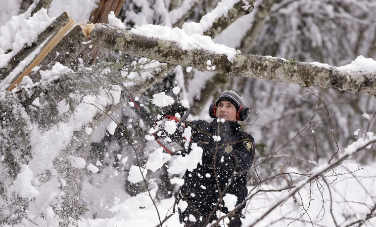 King County Sheriff's Deputy Peter Linde, a member of the county's search and rescue unit, uses a chainsaw to clear a partially fallen tree blocking a road Tuesday, Dec. 22, 2015, at Snoqualmie Pass, Wash. Linde said that a small group of hikers, who were without snowshoes, were in need of assistance in getting out of the area after a heavy overnight snow there. (AP Photo/Elaine Thompson)