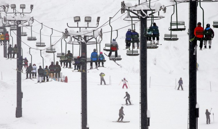 Skiers and snowboarders ride a lift up a mountain on Tuesday, Dec. 22, 2015, at Snoqualmie Pass, Wash. A weather pattern that could be associated with El Nino has turned winter upside-down across the U.S. during a week of heavy holiday travel, bringing spring-like warmth to the Northeast, a risk of tornadoes in the South and so much snow in parts of the West that there are concerns about avalanches. (AP Photo/Elaine Thompson)