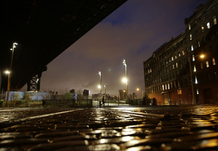A person walks under the Manhattan Bridge on a warm evening in the Brooklyn borough of New York on Tuesday, Dec. 22, 2015. In a reversal of a typical Christmas, forecasters expect New York to be in the mid-60s on the holiday — several degrees higher than Los Angeles. (AP Photo/Peter Morgan)