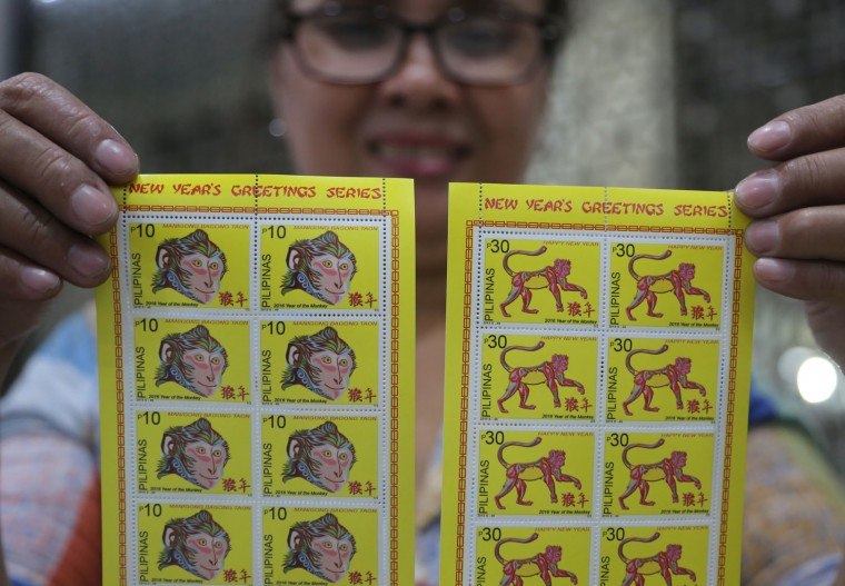 Employee Salome Arao poses as she holds 2016 Year of the Monkey commemorative stamps at the Philippine Post Office in Manila, Philippines on Monday, Dec. 28, 2015. Next year is the Year of the Monkey according to the Chinese zodiac. (AP Photo/Aaron Favila)