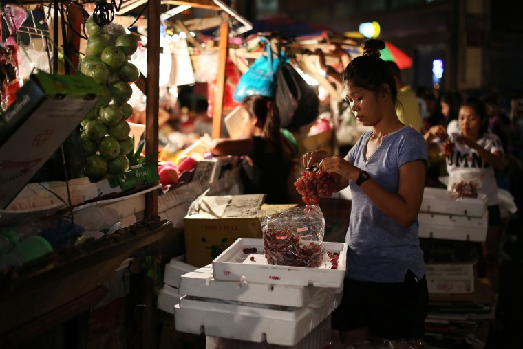 Sherry-Ann Abellar prepares grapes as she helps in the family-run business of selling fruits along makeshift stalls in downtown Manila, Philippines on Monday, Dec. 28, 2015. Many Filipinos believe that having 12 round fruits of different kinds on the family table will bring good luck during the New Year. (AP Photo/Aaron Favila)