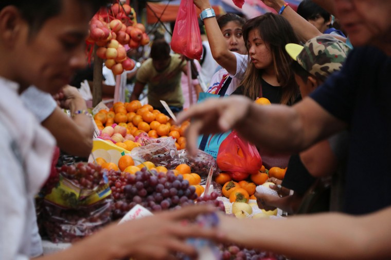 Filipinos buy round fruits along makeshift stalls in downtown Manila, Philippines on Monday, Dec. 28, 2015. Many Filipinos believe that having 12 round fruits of different kinds on the family table will bring good luck during the New Year. (AP Photo/Aaron Favila)