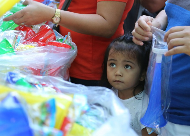 A Filipino girl looks as people buy plastic horns at makeshift stalls in downtown Manila, Philippines on Monday, Dec. 28, 2015. Many Filipinos believe that noisemakers will drive away evil spirits and bring good luck during the New Year. (AP Photo/Aaron Favila)