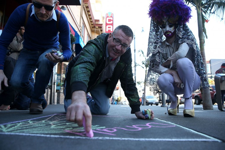 Joseph Leonardi writes the name of a person who died of AIDS on Castro Street on December 1, 2015 in San Francisco, California. To commemorate World AIDS day, dozens of people used chalk to write the names of people who have died from AIDS along San Francisco's Castro Street. World AIDS Day has been observed on December 1, since 1988, and is dedicated to raising awareness of the AIDS pandemic caused by the spread of HIV infection, and to mourn those who have died from the disease. (Photo by Justin Sullivan/Getty Images)