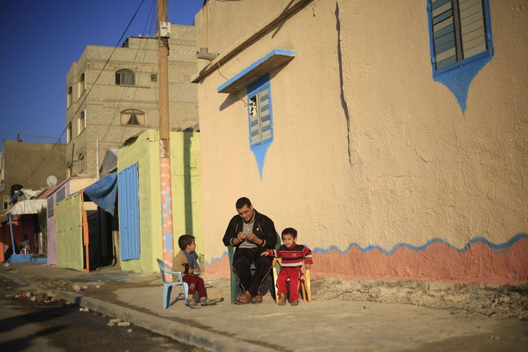 A Palestinian family sit outside their house painted by Palestinian artists in the al-Shati refugee camp in Gaza City, on November 12, 2015, as more than 30 artists take part in a project funded by Padico holding, a limited public shareholding company traded on the Palestine Exchange (PEX). (AFP Photo/Mohammed Abed)