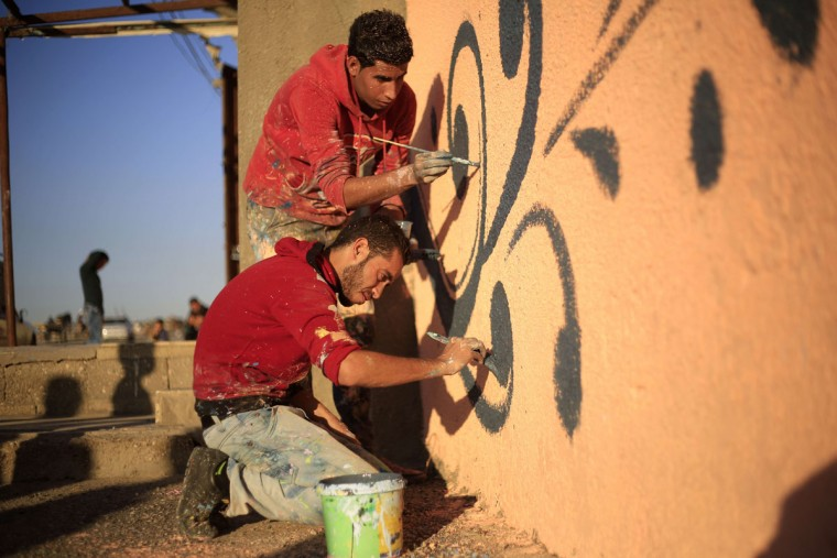 Palestinian artists paint the facade of a house in the al-Shati refugee camp in Gaza City, on November 12, 2015, as they take part in a project with more than 30 artists funded by Padico holding, a limited public shareholding company traded on the Palestine Exchange (PEX). (AFP Photo/Mohammed Abed)