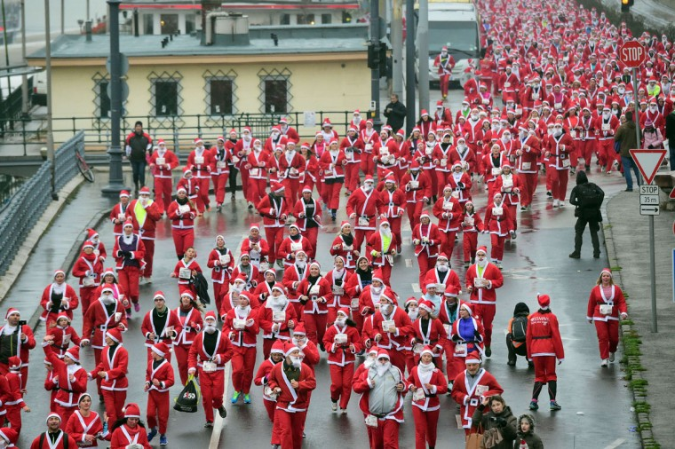 Runners wearing Santa Claus costumes take the start at the 'Santa Claus Run' at the bank of Danube River in downtown of Budapest on December 6, 2015. Thousand runners took part in this year's run. (AFP Photo/Attila Kisbenedek)