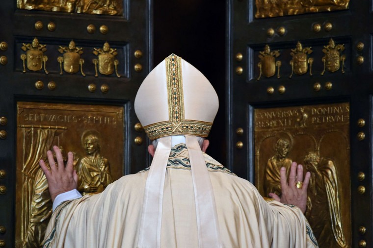 "Pope Francis opens a ""Holy Door"" at St Peter's basilica to mark the start of the Jubilee Year of Mercy, on December 8, 2015 in Vatican. In Catholic tradition, the opening of ""Holy Doors"" in Rome symbolises an invitation from the Church to believers to enter into a renewed relationship with God. (AFP Photo/Vincenzo Pinto)"
