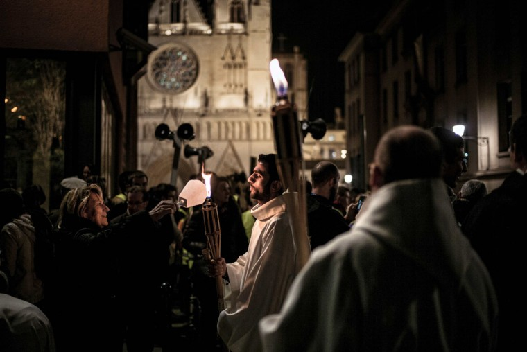 A woman lights a candle from a procession on December 8, 2015 in Lyon, as part of a city-wide tribute to victims of the November 13 Paris terrorist attacks, and as a replacement for the cancelled annual Festival of Lights, a secular version of a religious tradition devoted to the Virgin Mary and dating back to 153 years ago. (AFP Photo/Jeff Pachoud)