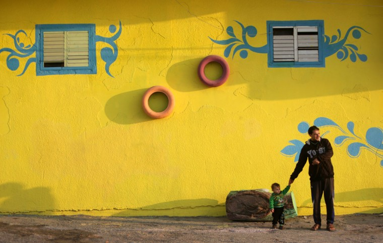 A Palestinian man and a boy stand in front of a house painted by Palestinian artists in the al-Shati refugee camp in Gaza City, on December 19, 2015. (AFP Photo/Mahmud )
