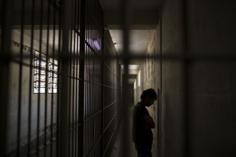 In this Nov. 30, 2015 photo, an inmate stands facing the wall as he waits for authorization to walk to his cell inside the Central Prison in Porto Alegre, Brazil. As with many nations in Latin America, the penitentiary system is chaotic and cruel, with violent uprisings across Brazil breaking out frequently as prisoners rebel against horrific conditions. (AP Photo/Felipe Dana)