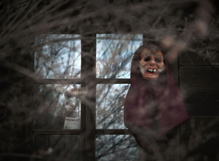 A mask hangs by the window of a wooden house during a show of winter traditions at the Village Museum in Bucharest, Romania, Sunday, Dec. 13, 2015. (AP Photo/Vadim Ghirda)