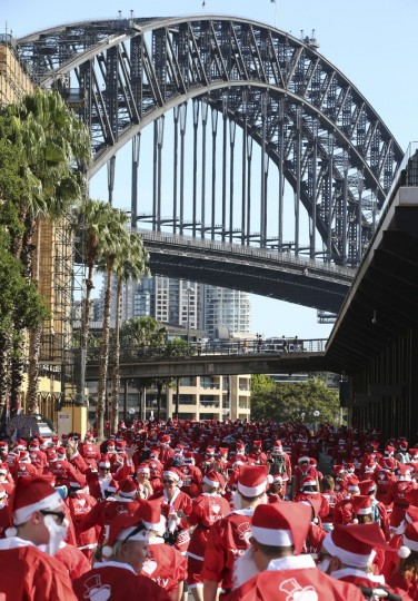 Thousands of people dressed in Santa Claus costumes make their way on a 5-kilometer course during the annual Santa Fun Run in Sydney Sunday, Dec. 6, 2015. The Santa Fun Run was organized by Variety, an Australian charity that helps children who are sick, disadvantaged or have special needs. (AP Photo/Rob Griffith)