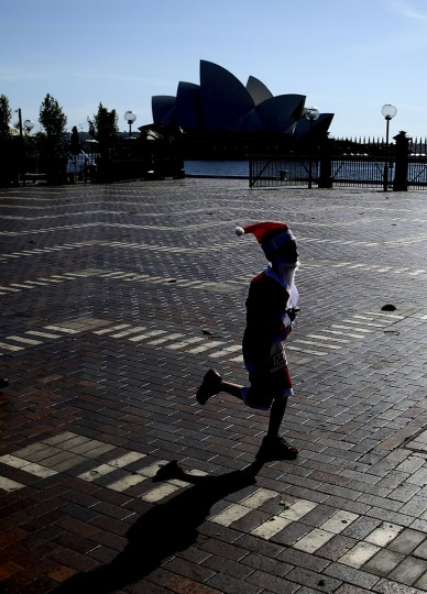 A boy dressed as Santa Claus makes his way to the finish line during the annual Santa Fun Run in Sydney Sunday, Dec. 6, 2015. The Santa Fun Run was organized by Variety, an Australian charity that helps children who are sick, disadvantaged or have special needs. (AP Photo/Rob Griffith)