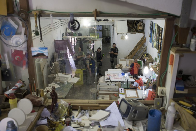 In this Nov. 30, 2015 photo, police officers watch prisoners creating art in a workshop at the Central Prison in Porto Alegre, Brazil. Inmates on work programs, voluntarily detoxing from drugs or from the LGBT community who are at high risk of being attacked, live in separate areas of the prison, but their special protection is unquestionably an exception. (AP Photo/Felipe Dana)