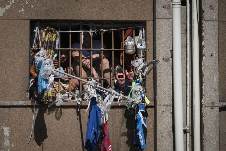 In this Nov. 30, 2015 photo, inmates peer from their cell window at the Central Prison in Porto Alegre, Brazil. One only catches glimpses of what goes on inside from behind tall metal fences topped with razor wire, where guards keep an anxious eye on inmates, packed 10 to a cell that should sleep only four. (AP Photo/Felipe Dana)