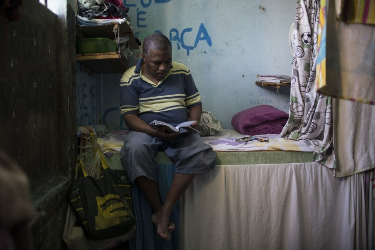 In this Nov. 30, 2015 photo, an inmate who joined a drug rehabilitation program reads inside his cell at the Central Prison in Porto Alegre, Brazil. Inmates on work programs, voluntarily detoxing from drugs or from the LGBT community who are at high risk of being attacked, live in separate areas of the prison, but their special protection is unquestionably an exception. (AP Photo/Felipe Dana)