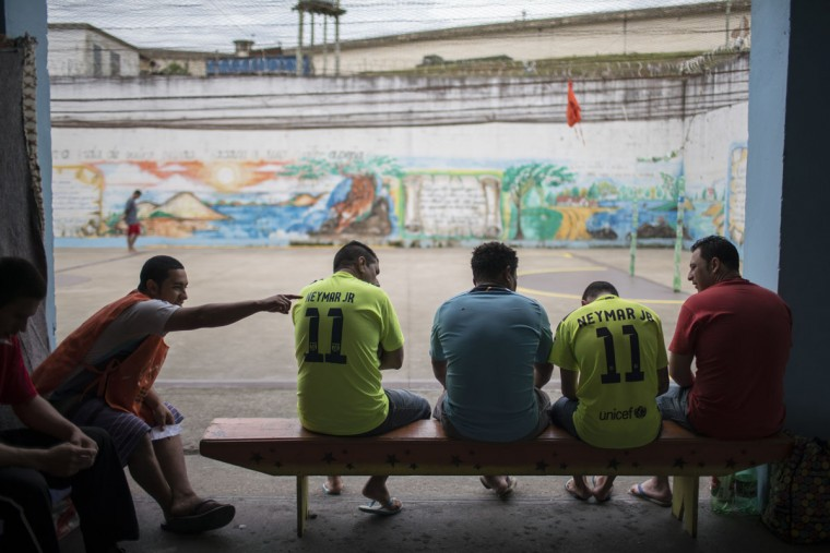 In this Dec. 1, 2015 photo, inmates chat inside the patio of a cell block set aside for working prisoners at the Central Prison in Porto Alegre, Brazil. Inmates on work programs, voluntarily detoxing from drugs or from the LGBT community who are at high risk of being attacked, live in separate areas of the prison, but their special protection is unquestionably an exception. (AP Photo/Felipe Dana)