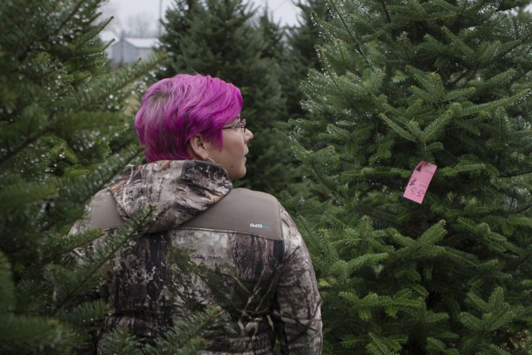 Jenny Lawson browses Christmas trees at the John T Nieman Nursery, Saturday, Nov. 28, 2015, in Hamilton, Ohio. (AP Photo/John Minchillo)