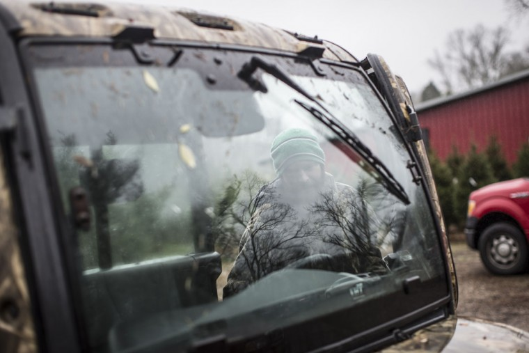 Arborist Tim Nieman is seen the window of a transport used to haul Christmas trees at the John T Nieman Nursery, Saturday, Nov. 28, 2015, in Hamilton, Ohio. (AP Photo/John Minchillo)