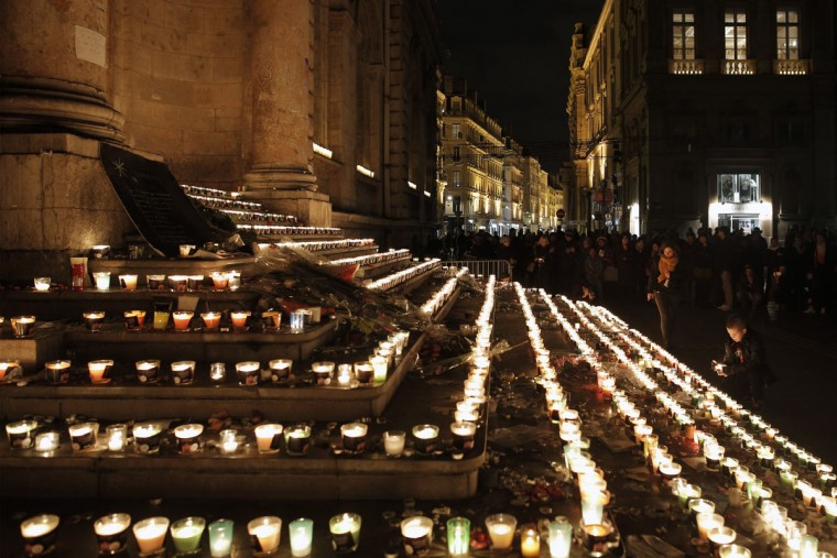 People light candles in front of the city hall building of Lyon, central France, Tuesday, Dec. 8, 2015, as part of a tribute to the 130 victims of the attacks in Paris. Each year, millions of visitors come into the city to watch the Festival des Lumieres, and this year the Lyon municipality has decided to cancel the festival to express solidarity with the victims. (AP Photo/Laurent Cipriani)