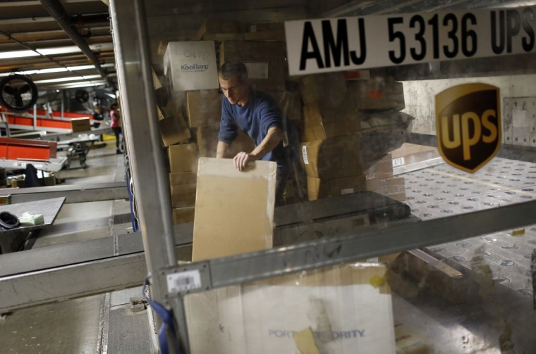 UPS employee Justin Sims prepares to place a package on a conveyor belt while unloading a container at Worldport in Louisville, Ky. Each container typically holds about 400 packages. (AP Photo/Patrick Semansky)