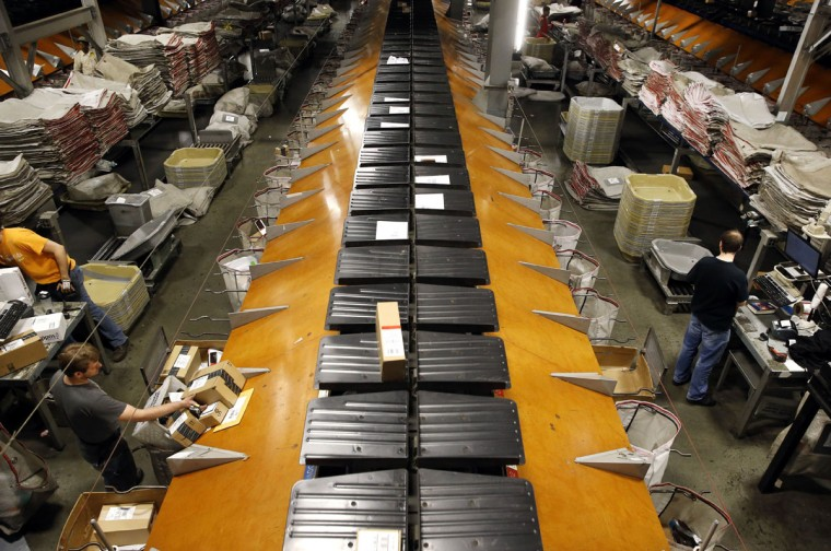 A conveyor belt carries envelopes and small packages past UPS workers to their destinations within Worldport in Louisville, Ky. Typically, it only takes 13 minutes for a parcel to travel the facility's web of belts and chutes. (AP Photo/Patrick Semansky)