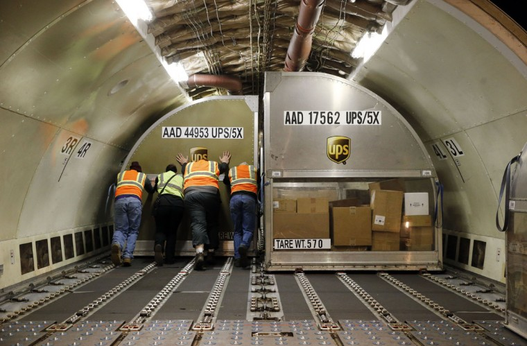 UPS workers push a container full of packages into place inside an airplane at Worldport in Louisville, Ky. In a five hour period at Worldport, 130 planes have landed, unloaded, reloaded and returned to the skies. (AP Photo/Patrick Semansky)