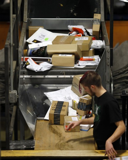 A UPS worker sorts packages, ensuring that shipping labels face up for reading by laser scanners, before placing them on a conveyor belt at Worldport in Louisville, Ky. On a typical night, 1.6 million packages pass through Worldport. Just before Christmas, there can be 4 million. (AP Photo/Patrick Semansky)